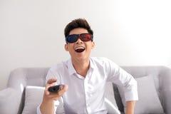 Stilig man i exponeringsglas som 3d sitter på soffan och hållande ögonen på tv arkivfoton