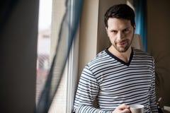 Stilig man i pajams bredvid fönster royaltyfri foto