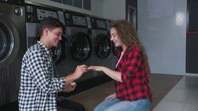 Stilig man i skjortadanandeförslag i tvätteri till den röda kvinnan för lockigt hår Hon säger ja lager videofilmer