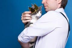 Stilig man i skjortan och svart hängslen som rymmer och slår den gulliga gråa katten i guld- krona på blå bakgrund royaltyfri bild