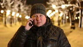 Stilig man i vintern som talar på hans telefon på en stadsgata på en frostig afton lager videofilmer