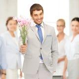 Stilig man med blommor i hand arkivfoto
