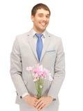 Stilig man med blommor i hand arkivbild