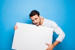 Stilig man med det tillfälliga klädda innehavet för skägg en tom panel på Arkivfoton