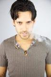 Stilig man med rök som kommer ut ur hans mun Fotografering för Bildbyråer