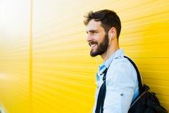 Stilig man med ryggsäcken på guling arkivfoto