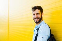 Stilig man med ryggsäcken på guling royaltyfria bilder