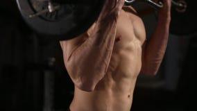 Stilig man med stora muskler som poserar i vikterna för muskulös man för idrottshall lyftande över muskulöst manarbete för mörk b arkivfilmer