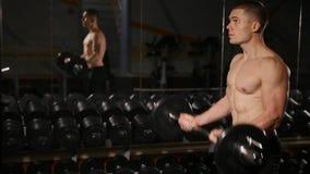 Stilig man med stora muskler som poserar i vikterna för muskulös man för idrottshall lyftande över muskulöst manarbete för mörk b stock video