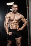 Stilig man med stora muskler som poserar på kameran i idrottshallen arkivbild