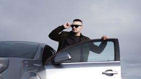 Stilig man nära bilen stående för man för glass livstid för konjakaffärscigarr lyxig arkivbild