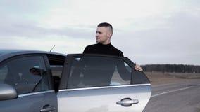Stilig man nära bilen stående för man för glass livstid för konjakaffärscigarr lyxig arkivbilder