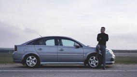 Stilig man nära bilen stående för man för glass livstid för konjakaffärscigarr lyxig fotografering för bildbyråer