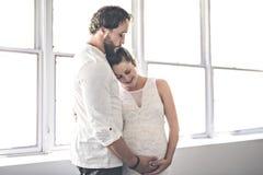 Stilig man och hans härliga gravida fruanseende nära fönstret hemma arkivfoto