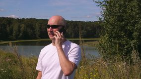 Stilig man som använder mobiltelefonen på flodlandskap i sommarskog arkivfilmer