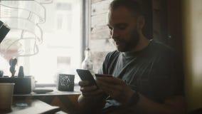 Stilig man som använder online-bankrörelsen från smartphonen som gör att shoppa direktanslutet med kreditkortsammanträde på kafét arkivfilmer