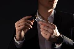 Stilig man som applicerar doft på hals mot svart bakgrund arkivbild