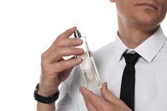 Stilig man som applicerar doft på hals mot vit bakgrund arkivbild