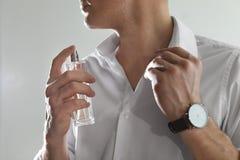 Stilig man som applicerar doft p? hals mot ljus bakgrund arkivfoton