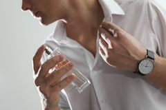 Stilig man som applicerar doft p? hals mot ljus bakgrund arkivbilder
