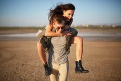 Stilig man som går med den nätta flickan på en baksida på en naturlig bakgrund Romantiker snubblar begrepp kopiera avstånd Royaltyfri Bild