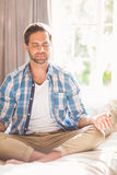 Stilig man som gör yoga på hans säng Arkivfoto