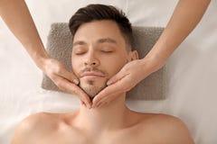 Stilig man som har ansikts- massage i brunnsortsalong royaltyfri foto