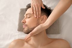 Stilig man som har ansikts- massage i brunnsortsalong arkivfoto