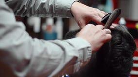 Stilig man som har en rakning med tappningrakkniven på frisersalongen stock video