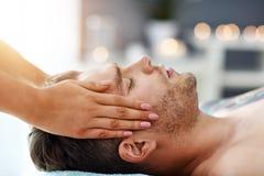 Stilig man som har massage i brunnsortsalong royaltyfri foto
