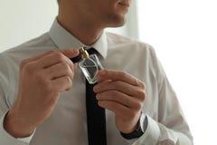 Stilig man som inomhus applicerar doft p? hals fotografering för bildbyråer