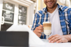 Stilig man som kopplar av med koppen av latte Arkivfoton