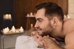 Stilig man som kopplar av p? massagetabellen i brunnsortsalong royaltyfri foto