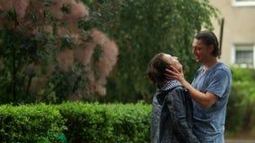 Stilig man som kysser hans flickvän med lockigt hår, medan regnar utomhus Stående av två vänner i regnet lager videofilmer