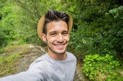 Stilig man som ler på kameran som tar en selfie i en skog royaltyfri fotografi