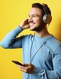 Stilig man som lictening till musik över gul bakgrund arkivfoto