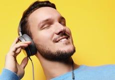 Stilig man som lictening till musik över gul bakgrund royaltyfri foto