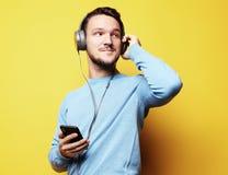 Stilig man som lictening till musik över gul bakgrund arkivbild
