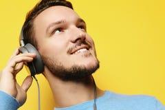 Stilig man som lictening till musik över gul bakgrund arkivfoton