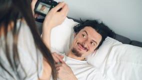 Stilig man som poserar med den roliga framsidan som skrattar när flicka som tar fotoet i säng stock video