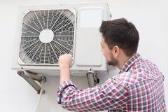 Stilig man som reparerar luftkonditioneringsapparaten Arkivfoton