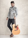 Stilig man som rymmer en akustisk gitarr mot grungeväggen Royaltyfri Bild