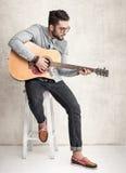 Stilig man som rymmer en akustisk gitarr mot grungeväggen Royaltyfria Bilder