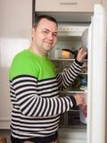 Stilig man som söker efter något i kylskåp arkivbild