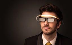 Stilig man som ser med futuristiska tekniskt avancerade exponeringsglas Royaltyfri Bild