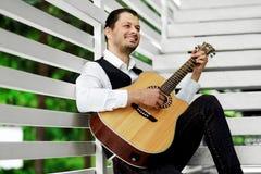 Stilig man som spelar gitarren på trappan Avslappnande attraktiv man som utomhus ler och royaltyfri foto