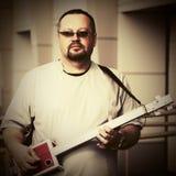 Stilig man som spelar hans gitarr för cigarrask Royaltyfri Bild