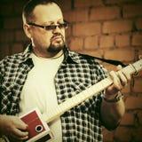 Stilig man som spelar hans gitarr för cigarrask Arkivfoton