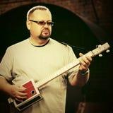 Stilig man som spelar hans gitarr för cigarrask Arkivbild