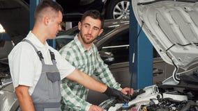 Stilig man som talar till bilmekanikern på reparationsstationen royaltyfri fotografi